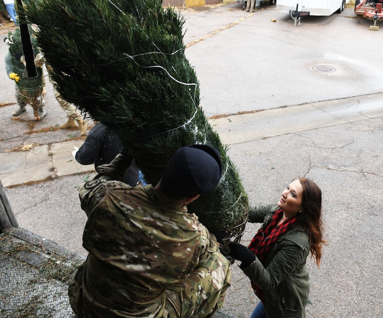 Chelsey Mastalski, the 28th Force Support Squadron outdoor recreation manager, unloads a tree from a truck at Ellsworth Air Force Base, S.D., Nov. 30, 2018. Trees for Troops is an event where community members all over the country donate trees to service members so they can have a free tree for the holidays. (U.S. Air Force photo by Airman 1st Class Thomas Karol)