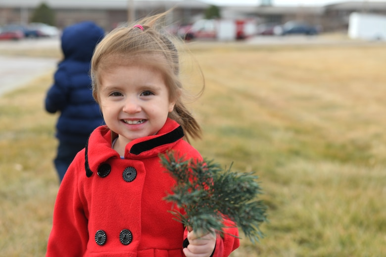 A child holds a branch while searching for tree at outdoor recreation on Ellsworth Air Force Base, S.D., Nov. 30, 2018. Trees for Troops is an event where community members all over the country donate trees to service members so they can have a free tree for the holidays. (U.S. Air Force photo by Airman 1st Class Thomas Karol)