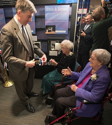 Photo of NSA Deputy Director John C. (Chris) Inglis hands a piece of the ribbon to Helen Nibouar (l) and Marion Johnson (r).