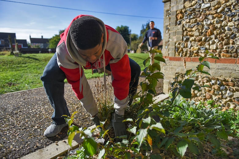 U.S. Air Force Staff Sgt. Kenneth Hummons, weeds along St. John's Church during a volunteer event in Beck Row, England, Sept. 29, 2018. Approximately 20 individuals to volunteered to clean the church. (U.S. Air Force photo by Staff Sgt. Christine Groening)