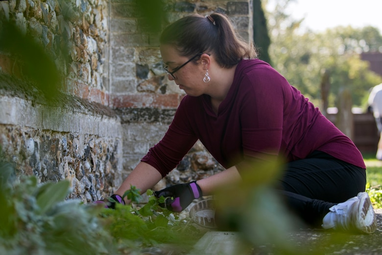 U.S. Air Force Tech. Sgt. Holly Lodin, weeds along St. John's Church during a volunteer event in Beck Row, England, Sept. 29, 2018. Volunteers from the 48th Fighter Wing and Team Mildenhall painted, pulled weeds and cleaned the grounds of the church. (U.S. Air Force photo by Staff Sgt. Christine Groening)