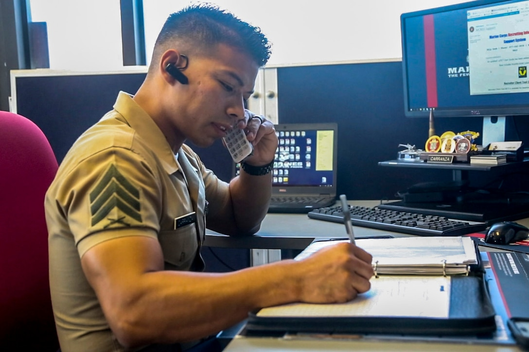 A Marine talks on the phone while sitting at a desk.