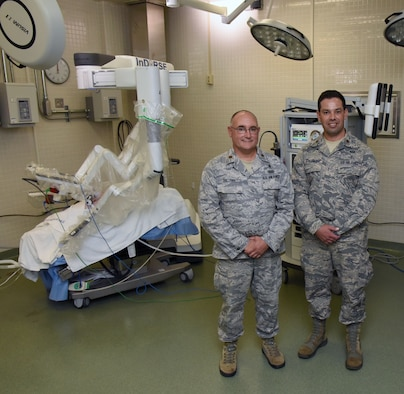 U.S. Air Force Maj. Joshua Tyler, 81st Surgical Operations Squadron Institute for Defense Robotic Surgical Education program director, Keesler Air Force Base, Miss., and Maj. Scott Thallemer, InDoRSE program coordinator, pose for a photo inside the robotics surgery training room at the clinical research lab on Keesler Air Force Base, Mississippi, Sept. 13, 2018. (U.S. Air Force photo illustration by Kemberly Groue)