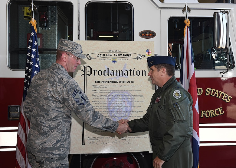 """U.S. Air Force Col. Christopher Amrhein, 100th Air Refueling Wing commander, shakes hands with U.S. Air Force Chief Master Sgt. William Taylor, 100th Civil Engineering Squadron installation fire chief, after the signing of the 2018 Fire Prevention Week Proclamation at RAF Mildenhall, England, Sept. 13, 2018.  Fire Prevention Week is Oct. 7 – 13, and this year's theme is """"Look, Listen, Learn."""" The fire department has a variety of events schedule for throughout the week for Team Mildenhall members and their families. (U.S. Air Force photo by Senior Airman Luke Milano)"""