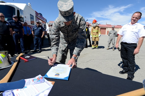 Brig. Gen. E. John Teichert III, 412th Test Wing commander, signs this year's Fire Prevention Week Proclamation as Mike Pinan, Edwards AFB Fire Prevention assistant chief (right) watches, Sept. 25. The general signed the proclamation while visiting with the 812th Civil Engineer Squadron. (U.S. Air Force photo by John Perry)