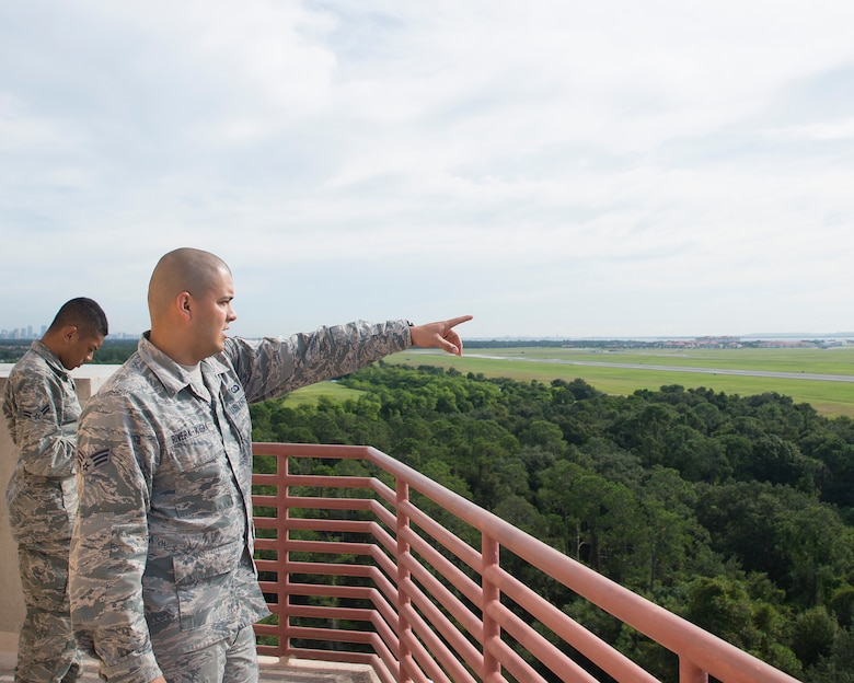 U.S. Air Force Senior Airman Daryl Rivera-Rivera, air traffic control journeyman assigned to the 6th Operation Support Squadron, and Airman 1st Class Julian Hurrey, air traffic control apprentice assigned to the 6th OSS, examine the flightline at MacDill Air Force Base, Florida, Oct. 1, 2018.