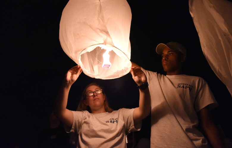 U.S. Air Force Airman 1st Class Tory Battles, and Airman Stephen Chapa, 336th Training Squadron students, prepare to let go of a sky lantern during a sky lantern vigil on Biloxi Beach, Mississippi, Sept. 27, 2018. In recognition of suicide prevention and awareness month, the 81st Medical Operations Squadron mental health team hosted the themed event, Lights For Life, to honor the memories of victims of suicide. (U.S. Air Force photo by Kemberly Groue)