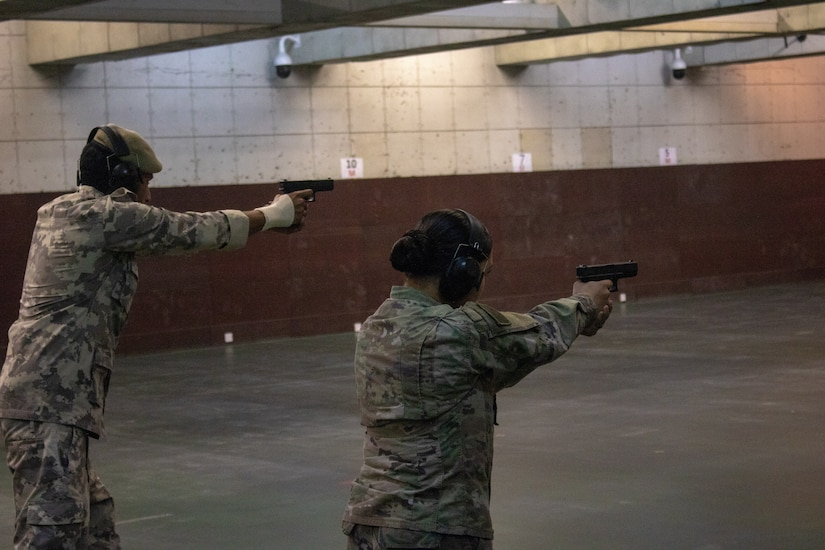 Spc. Alizon Gonzalez, Alpha Company, 578th Brigade Engineer Battalion, fires a handgun alongside an officer from the Qatar Central General Depot at the Qatar Special Forces range compound, Sep. 9, 2018. The range event provided a unique opportunity for Soldiers to build rapport with the Qatari soldiers from a Qatari base near Camp As Sayliyah.