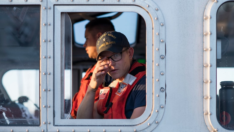 A U.S. Coast Guardsman looks out the side of a boat during a full mission profile exercise at Oxnard, Calif., Sept. 18, 2018. Airmen boarded a U.S. Coast Guard boat and tested search and rescue operations with cooperating aircraft. An FMP provides participants the opportunity to refine their tactics, techniques and procedures in operating in a maritime environment. (U.S. Air Force photo by Staff Sgt. Michael Washburn)