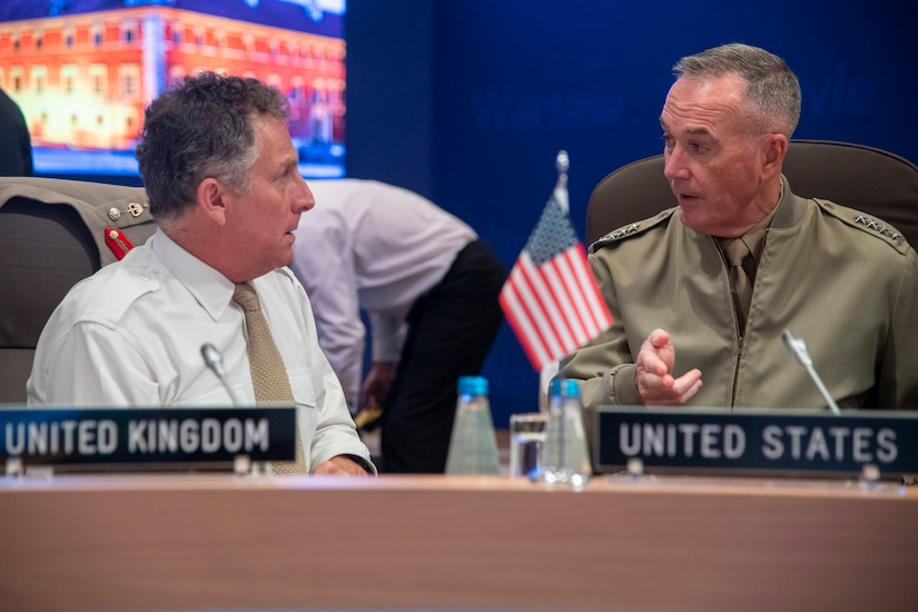 Marine Corps Gen. Joe Dunford, chairman of the Joint Chiefs of Staff, speaks to British Army Gen. Sir Nicholas Carter, chief of the defense staff, prior to the start of a session during the NATO Military Committee Conference in Warsaw, Poland.