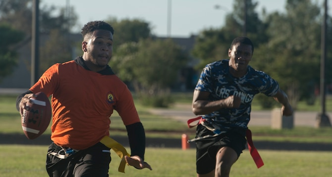 A player from the 97th Operations Support Squadron football team runs from a player from the 97th Logistics Readiness Squadron football team during the 97th Air Mobility Wing Flag Football Championships Sept. 28, 2018 on Altus Air Force Base, Okla. The 97th OSS and LRS played two games against each other with OSS winning the first, and LRS winning the second game to become the champions. (U.S. Air Force photo by A1C Jeremy Wentworth)