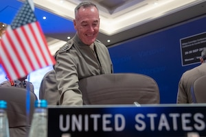 "Marine Corps Gen. Joe Dunford smiles while preparing to sit at a table, with a mini American flag and a ""United States"" placard."