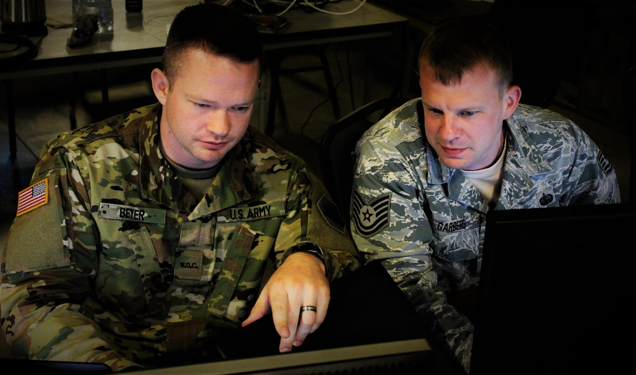 Two men sit at a computer.