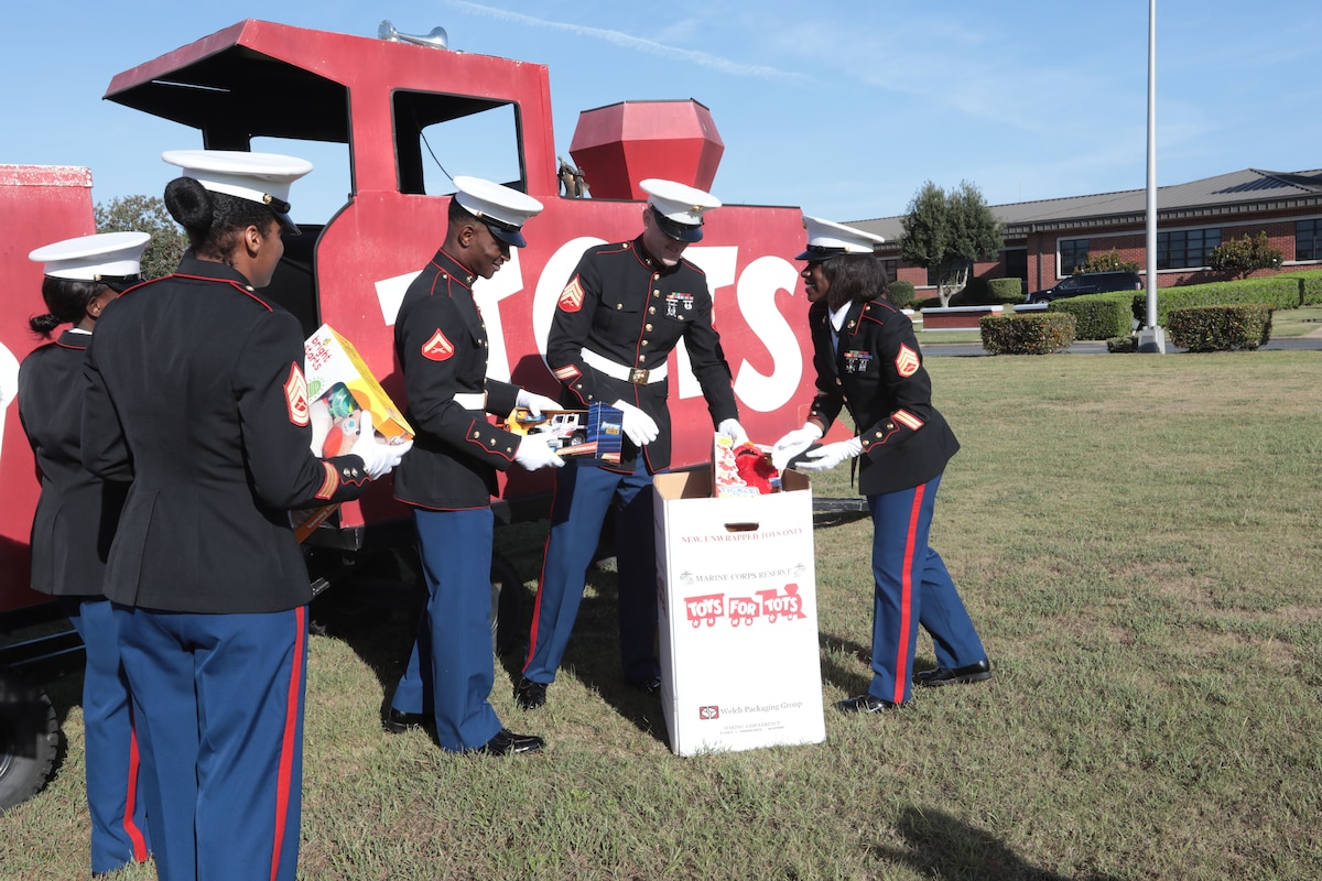 Several Marines put toys into a cardboard box