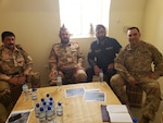 U.S. Army Capt. Vicente Garcia, far right, poses for a group photo with three district chiefs of police during an expeditionary advisory package at Zharay Province in Afghanistan, held on Aug. 8, 2018.