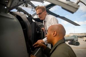 Navy undersecretary examines helicopter component.