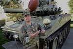 Idaho Army National Guard Capt. A.J. Edwards poses for a photo while tossing a football Sept. 27, 2018, on Gowen Field, Boise, Idaho. Edwards was struck by lightning on Sept. 30, 1998, at a football practice in Inkom, Idaho. He was wearing the helmet and holding the football shown. His teammates signed the football.