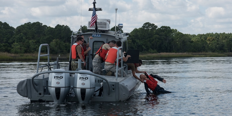 Sailors and Airmen participate in man overboard drills during a Shore Installation Management Basic Boat Coxswain Course Sept. 26, 2018, at Joint Base Charleston's Naval Weapons Station, S.C. The SIMBBCC curriculum arms security forces members with skills needed to conduct harbor patrol missions and covers techniques including man overboard drills, pier approaches, towing and anchoring.