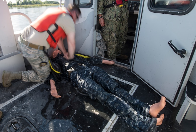U.S. Air Force Staff Sgt. Curtis March, 628th Security Forces Squadron patrolman, demonstrates CPR during a SIMBBC course Sept. 26, 2018, at Joint Base Charleston's Naval Weapons Station, S.C. The SIMBBCC curriculum arms security forces members with skills needed to conduct harbor patrol missions and covers techniques including man overboard drills, pier approaches, towing and anchoring.