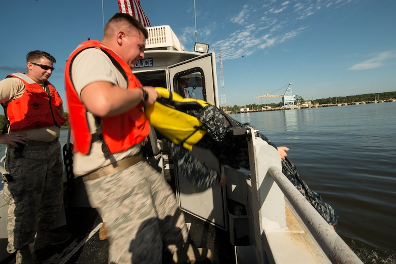 U.S. Air Force Senior Airman Ryan Olson, 628th Security Forces Squadron patrolman, pulls a mannequin out of the water during a man overboard drill during a Shore Installation Management Basic Boat Coxswain Course practical exercise Sept. 26, 2018, at Joint Base Charleston's Naval Weapons Station, S.C. The SIMBBCC curriculum arms security forces members with skills needed to conduct harbor patrol missions and covers techniques including man overboard drills, pier approaches, towing and anchoring.