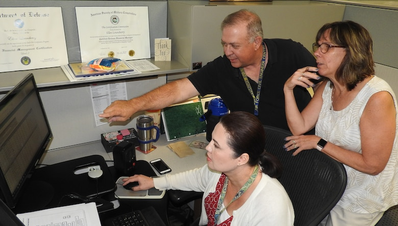 Linda Alcala, right, reviews time cards of civilians impacted by Hurricane Florence with members of her AFIMSC Financial Operations team, Ellen Lounsberry, seated, and Rick Baltes. U.S. Air Force Photo by Ed Shannon