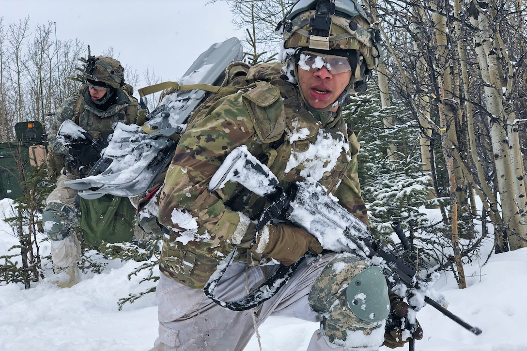 A soldier walks through the snow with a rifle.