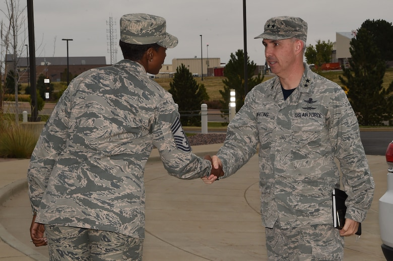 Chief Master Sgt. Tamar Dennis, 460th Space Wing command chief, greets Maj. Gen. Stephen Whiting, 14th Air Force commander, Air Force Space Command Sept. 28, 2018, on Buckley Air Force Base, Colorado. Whiting is responsible for leading and guiding a diverse team of Airmen charged with protecting and defending critical U.S. and allied space capabilities. (U.S. Air Force photo by Senior Airman Codie Collins)