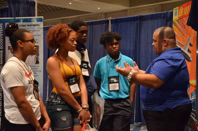 James Griffieth, a member of the Air Force Technical Applications Center, explains how a tesla coil works to students from Flint, Mich., who were attending the National Organization of Black Chemists and Chemical Engineers annual conference in Orlando Sept. 18, 2018.  The students competed in NOBCChE's Science Bowl the day before.  Pictured with Griffieth from left to right are students from Flint Southwester Classical Academy:  Brook Fordham, 16; Alayna Goff, 17; Kwame Wade, 16; and Keishaun Wade, 17.(U.S. Air Force photo by Susan A. Romano)