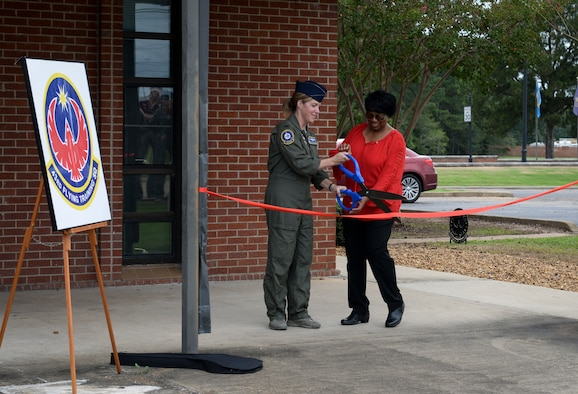 Col. Samantha Weeks, 14th Flying Training Wing commander, and Elaine Hobson, former 43rd Flying Training Squadron secretary, cuts the ribbon at the dedication ceremony Sept. 28, 2018, on Columbus Air Force Base, Mississippi. The 43rd FTS is one of several units at Columbus AFB that aids in creating pilots.  (U.S. Air Force photo by Airman Hannah Bean)