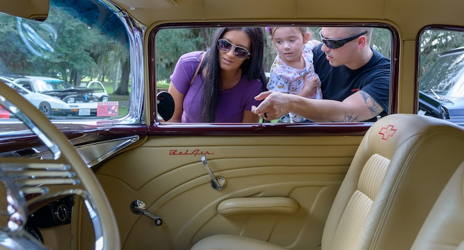 U.S. Navy Aviation Electrician Technician 2nd Class Pat Heffner, Center for Naval Aviation Technical Training Unit Keesler instructor, his wife, Heather, and daughter, Juliana, look at a 1957 Chevrolet Bel Air during the 15th Annual Cruisin' Keesler Car Show at Marina Park at Keesler Air Force Base, Mississippi, Sept. 29, 2018. The event is held to kick off Cruisin' the Coast, a festival to celebrate classic cars, trucks and hot rods, where vehicles cruise down the 30-mile beachside highway in Mississippi. The event welcomed visitors, classic vehicles and presented several awards presentations. (U.S. Air Force photo by Andre' Askew)
