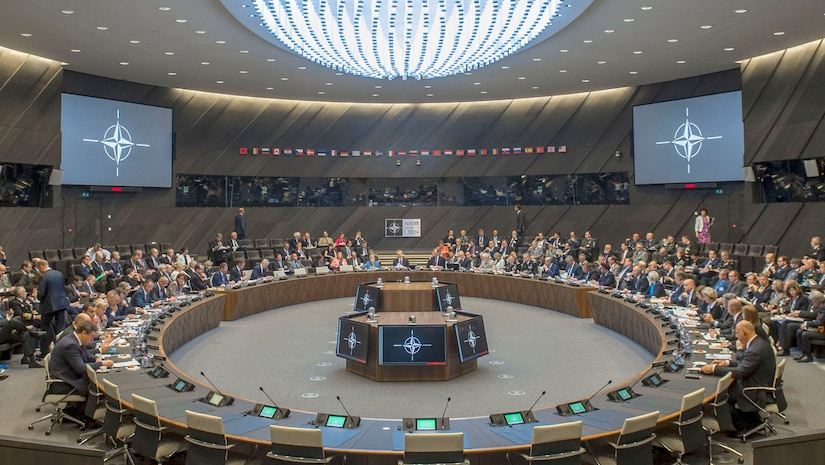 Defense ministers meet at the NATO headquarters in Brussels. A large conference room features a round table in the center of the image. More than 100 people are present.