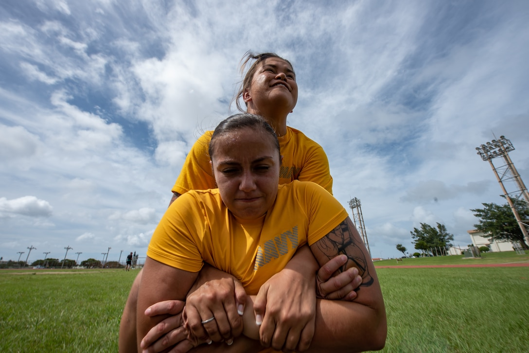 U.S. Navy Petty Officer 3rd Class Emily Pall carries Petty Officer 2nd Class Eva Aguilar, both Okinawa Joint Experience Green Team students, during the Okinawa Joint Fitness Challenge Sept. 26, 2018, at Kadena Air Base, Japan. The OJFC was designed to mimic obstacles and challenges faced in the battlefield such as sprinting, running ammunition cans, transporting wounded personnel to safety and tossing simulated grenades. Each team competed for the best time, however the final challenge brought all four teams together. (U.S. Air Force photo by Staff Sgt. Micaiah Anthony)