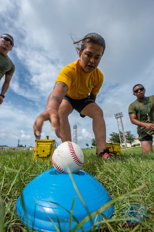 U.S. Navy Petty Officer 3rd Class Emily Pall, Okinawa Joint Experience Green Team student, reaches for a baseball during the Okinawa Joint Fitness Challenge Sept. 26, 2018, at Kadena Air Base, Japan. During the challenge, baseballs were used to simulate grenades. Teams were deducted points based on the accuracy of their throws. (U.S. Air Force photo by Staff Sgt. Micaiah Anthony)
