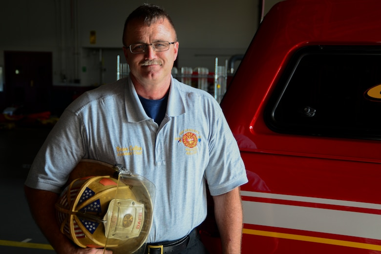 Brian Cullen, 436th Civil Engineer Squadron assistant fire chief, poses for a picture with a firefighter helmet at Dover Air Force Base, Del., Sept. 26, 2018. According to Cullen, safety measures for firefighters have changed dramatically from when he first started in 1980. (U.S. Air Force photo by Airman 1st Class Jonathan W. Harding)