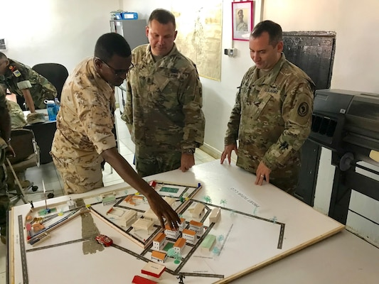 Forces Armee Djibouti (FAD) Lt. Meraneh, liaison officer, explains design and construction planning to Kentucky Guardsmen Command Sgt. Maj. Jerry Sipe, 201st Engineer Battalion, and Maj. Christopher Hettinger, Bilateral Affairs Officer for the State Partnership Program in Djibouti, at an Engineer Regiment Camp, Sept. 23, 2018. As part of the State Partnership Program, Service members from Kentucky and Djibouti met to discuss engineering best practices.