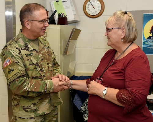 Col. (Dr.) Jerome Buller (left), commander of the U.S. Army Institute of Surgical Research at Joint Base San Antonio-Fort Sam Houston, presents Claudia Wood with a command coin Sept. 26 for 50 years of federal service. Wood, a supply technician at the USAISR, retired during an informal ceremony and potluck lunch Sept. 27.
