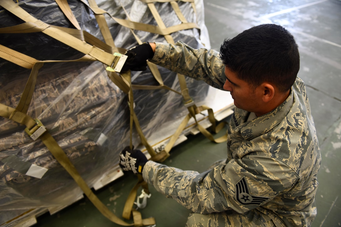 U.S. Air Force Staff Sgt. Joseph Needham, 92nd Logistics Readiness Squadron NCO in charge of passenger services, straps down cargo in preparation for loading at Fairchild Air Force Base, Washington, September 2018. Mobility Airmen fuel the fight, provide airlift needed for supplies and personnel, and enable versatile and timely effects through contingency response ensuring mission success. (U.S. Air Force photo/Airman 1st Class Lawrence Sena)