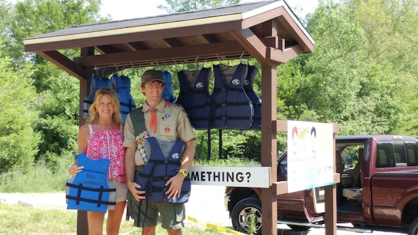 Matthew Mulcahy and his mother at the Life Jacket Loaner Kiosk he created for his Eagle Scout award.