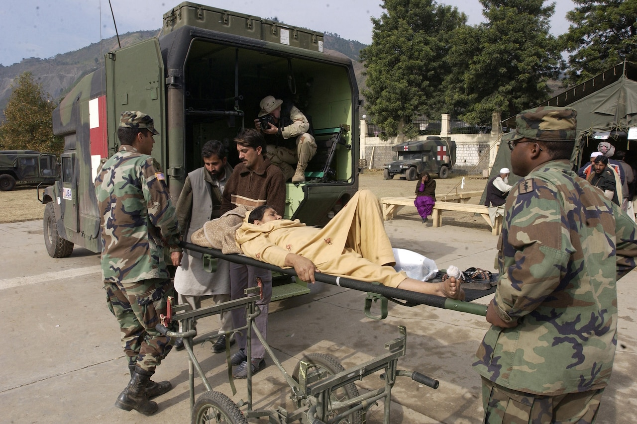 Soldiers hold a woman on a stretcher outside an ambulance.