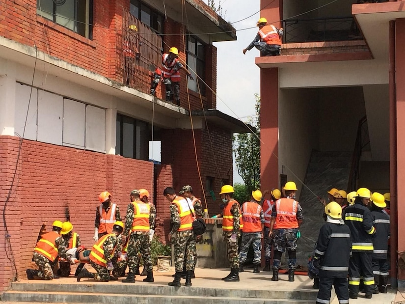 First responders in orange vests and camo pants gahter outside a building, as several of them maneuver on second-floor structures.