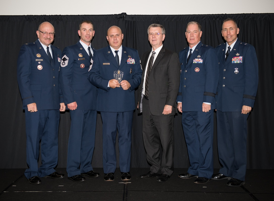 Chief Master Sgt. Donald Souron, 157th Security Forces Squadron (157th SFS), New Hampshire, receives the Air National Guard Outstanding Air Reserve Component Security Forces Airman of 2017 Award on behalf of the actual recepient, Senior Airman Brandan Abel, 157th SFS, at the 2018 Air National Guard Security Forces Squadron Dinner and Awards Banquet at the National Center for Employee Development Conference Center in Norman, Oklahoma, Sept. 12, 2018. Every year, leadership from all of the Air National Guard security forces squadrons meet in one place to discuss past, current and upcoming topics that impact the career field, as well as recognize outstanding security forces Airmen. (U.S. Air National Guard Photo by Staff Sgt. Kasey M. Phipps)