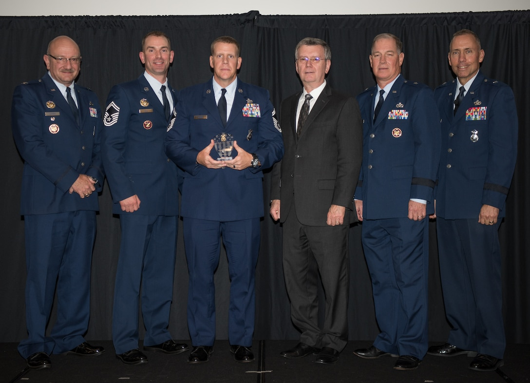 Senior Master Sgt. Adam Jessee, 183rd Air Component Operations Squadron, Abraham Lincoln Capital Airport, Illinois, receives the Air National Guard Outstanding Security Forces Support Staff Senior Noncommisioned Officer of 2017 Award at the 2018 Air National Guard Security Forces Squadron Dinner and Awards Banquet at the National Center for Employee Development Conference Center in Norman, Oklahoma, Sept. 12, 2018. Every year, leadership from all of the Air National Guard security forces squadrons meet in one place to discuss past, current and upcoming topics that impact the career field, as well as recognize outstanding security forces Airmen. (U.S. Air National Guard Photo by Staff Sgt. Kasey M. Phipps)