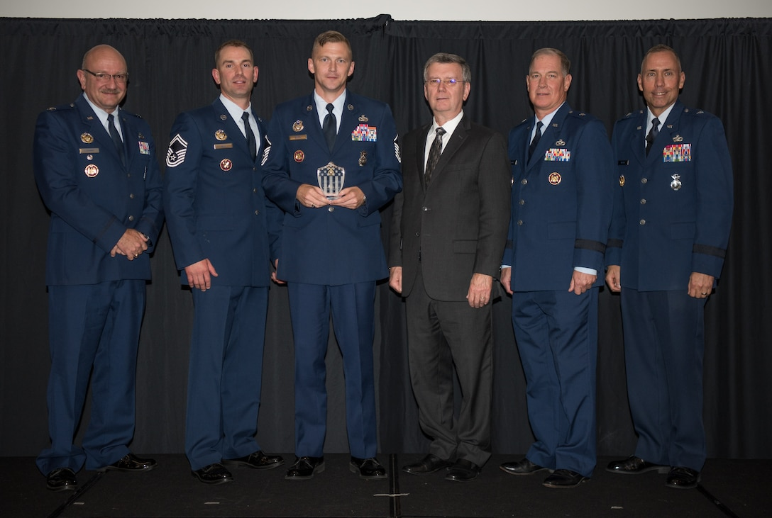 Master Sgt. Olen Smith III, National Guard Bureau/Air National Guard Security Forces Division, Joint Base Andrews, Maryland, receives the Air National Guard Higher Headquarters Staff Noncommissioned Officer of 2017 Award at the 2018 Air National Guard Security Forces Squadron Dinner and Awards Banquet at the National Center for Employee Development Conference Center in Norman, Oklahoma, Sept. 12, 2018. Every year, leadership from all of the Air National Guard security forces squadrons meet in one place to discuss past, current and upcoming topics that impact the career field, as well as recognize outstanding security forces Airmen. (U.S. Air National Guard Photo by Staff Sgt. Kasey M. Phipps)