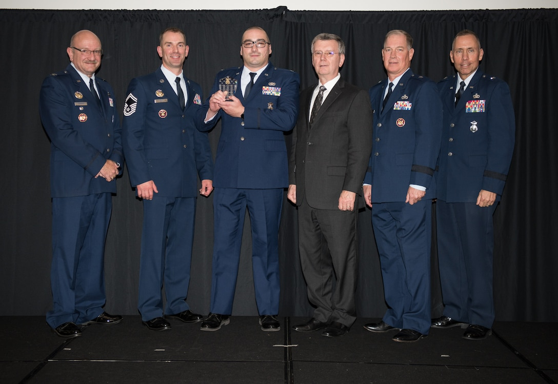 """Capt. Aaron McCarthy, 157th Security Forces Squadron (157th SFS), Pease Air National Guard Base, New Hampshire, receives the Air National Guard Staff Sgt. Todd """"TJ"""" Lobraico Award for Excellence on behalf of the actual recepient, Senior Master Sgt. Dale Snowdon, 157th SFS, at the 2018 Air National Guard Security Forces Squadron Dinner and Awards Banquet at the National Center for Employee Development Conference Center in Norman, Oklahoma, Sept. 12, 2018. Every year, leadership from all of the Air National Guard security forces squadrons meet in one place to discuss past, current and upcoming topics that impact the career field, as well as recognize outstanding security forces Airmen. (U.S. Air National Guard Photo by Staff Sgt. Kasey M. Phipps)"""