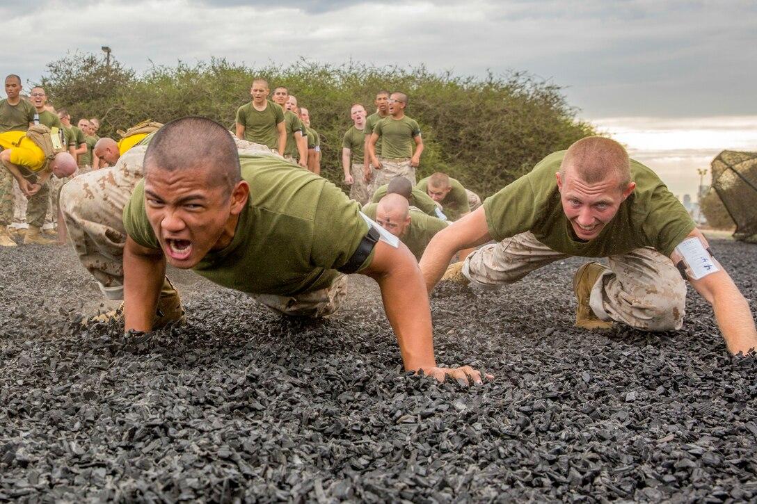 Marines crawl over gravel.