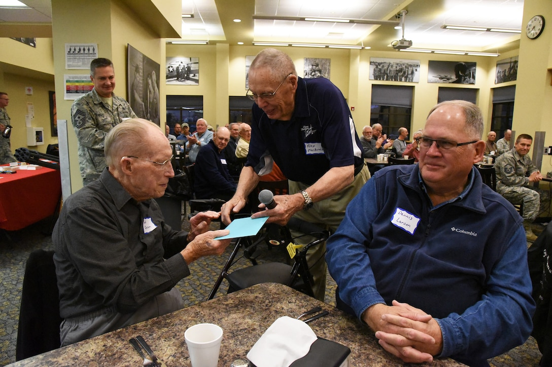 Retired Maj. Gen. Alexander Macdonald, a former 119th Wing commander and North Dakota adjutant general, presents a birthday card to retired Chief Master Sgt. Fred Quam for his 102nd birthday, which was Oct. 2, during an annual retiree breakfast get-together at the North Dakota Air National Guard Base, Fargo, N.D., Oct. 3, 2018.