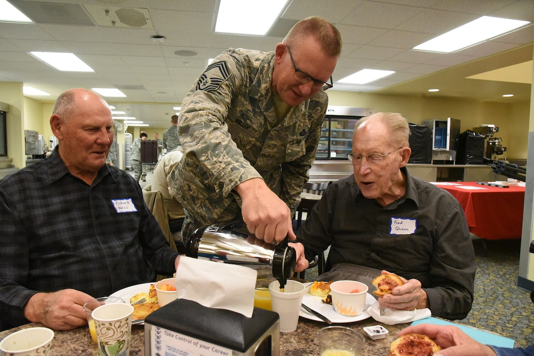 Chief Master Sgt. Jeff Miller pours coffee for retired Chief Master Sgt. Fred Quam at the annual retiree breakfast get-together at the North Dakota Air National Guard Base, Fargo, N.D., Oct. 3, 2018.