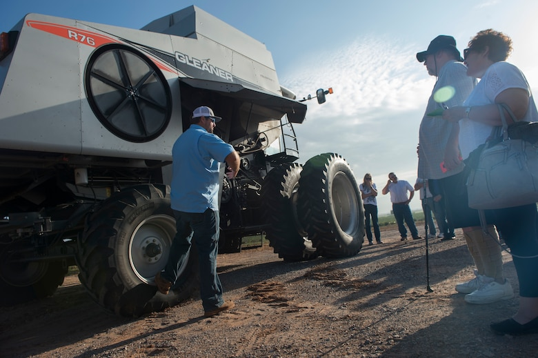 A man talking to people in front of a tractor
