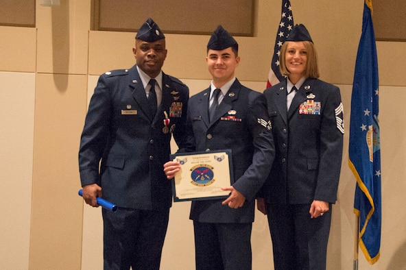 Lt. Col. Erick Welcome, 460th Space Communications Squadron outgoing commander, and Chief Master Sgt. Tammie Gaudu, 460th SCS superintendent, present Airman 1st Class Geordan Penners, 460th SCS technician, with senior airman below-the-zone, June 28, 2018, on Buckley Air Force Base, Colorado. The BTZ program allows recipients to promote to senior airman six months ahead of their peers. (U.S. Air Force photo by Senior Airman Stephen Eigel)
