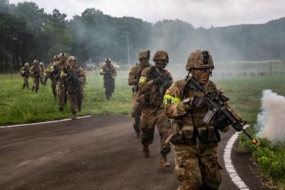 Soldiers in battle gear cross a road.